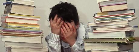 Una bambina tra i libri di scuola