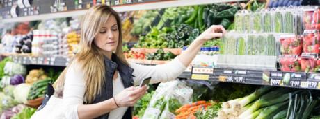La spesa al supermercato valutando i cibi con lo smartphone