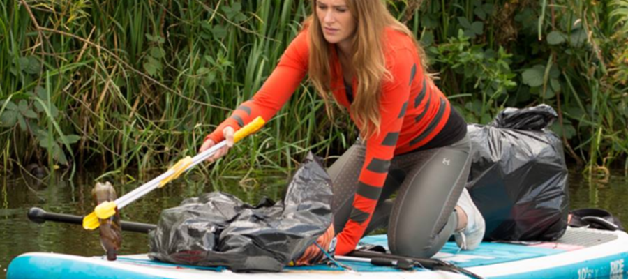 La ragazza che raccoglie plastica col surf