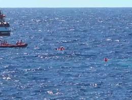 I migranti che si lanciano in mare dalla Open Arms